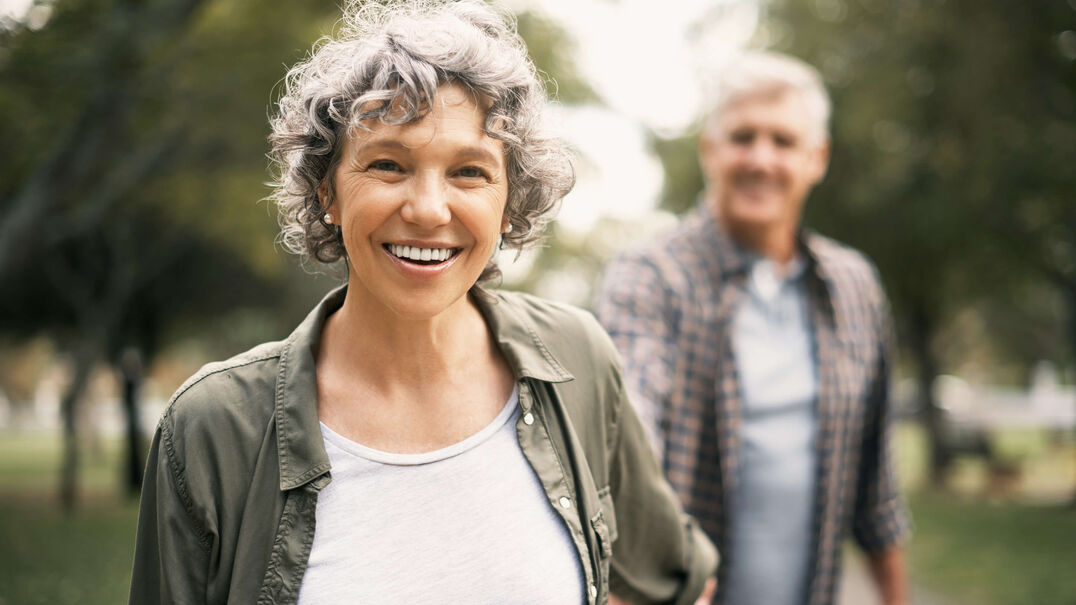 A smiling middle-aged couple are walking hand-in-hand in the park.